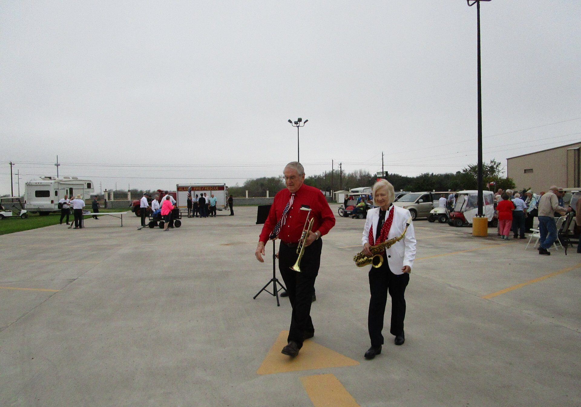 Dr. Chipchase and Mrs. Chipchase carry their instruments after playing for the flag retirement ceremony